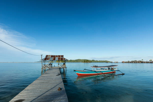 Wooden pier with boat in Togean islands of Sulawesi In the remote Togean islands in Central Sulawesi province of Indonesia, local Bajo people live by the sea and near the sea. This wooden pontoon of a local bungalow resort, is used by local boats to deliver goods and travel. sulawesi stock pictures, royalty-free photos & images
