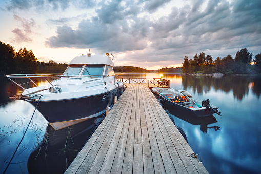 Wooden pier with boat at sunset