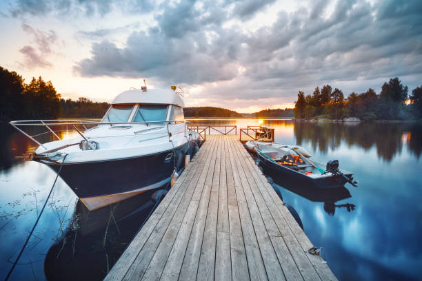Wooden pier with boat Wooden pier with boat at sunset bay of water stock pictures, royalty-free photos & images