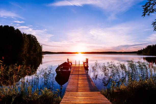 Wooden pier with fishing boat at sunset on a lake in Finland Wooden pier with fishing boat at sunset on a lake in rural Finland lake stock pictures, royalty-free photos & images