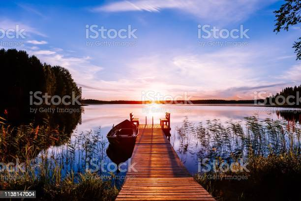 Photo of Wooden pier with fishing boat at sunset on a lake in Finland
