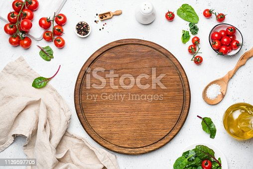 Wooden pizza board and pizza cooking ingredients on white concrete background. Table top view. Copy space for text, recipe, restaurant or cafe menu