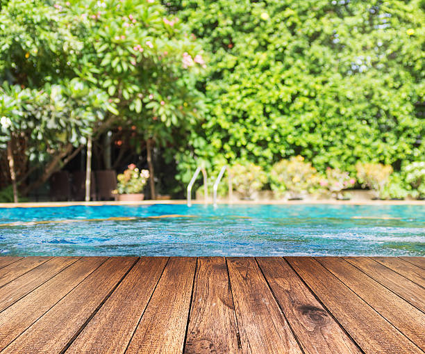 Wooden plank floor against swimming pool with green trees Wooden plank floor against swimming pool with green trees. Travel, relaxation background. Text space poolside stock pictures, royalty-free photos & images