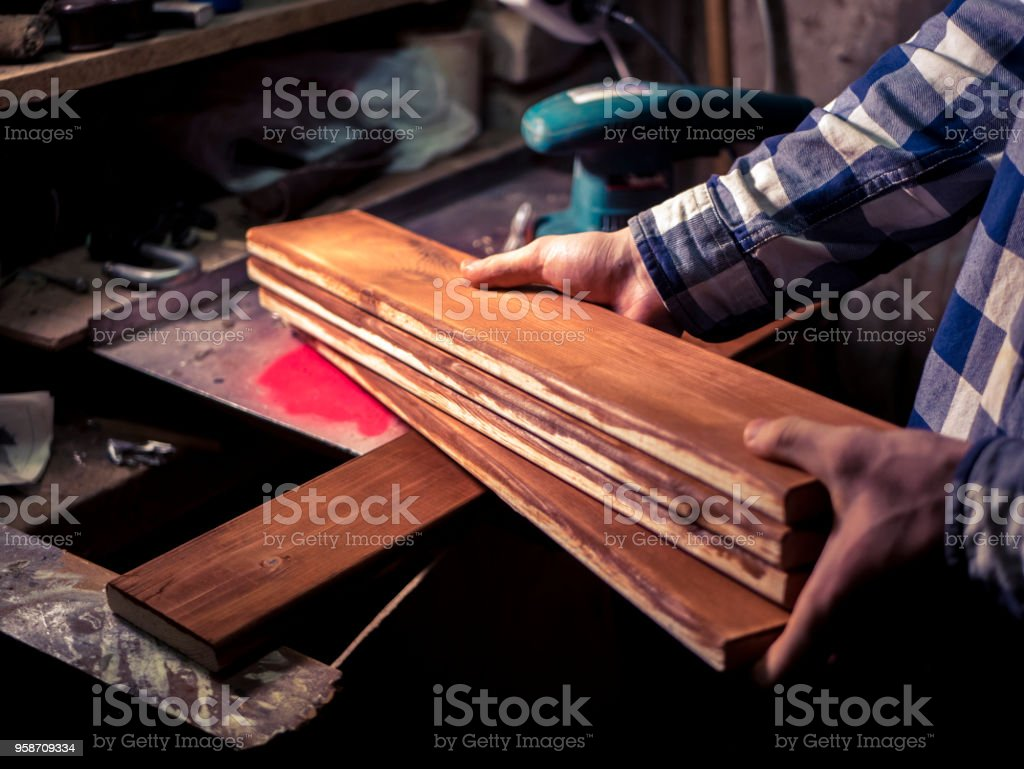 wooden plank in the hand of man working in the dark room stock photo