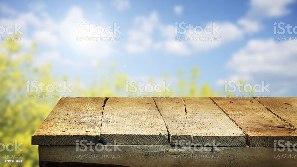 Wooden planks of a table with a blurred view of the sky  stock photo