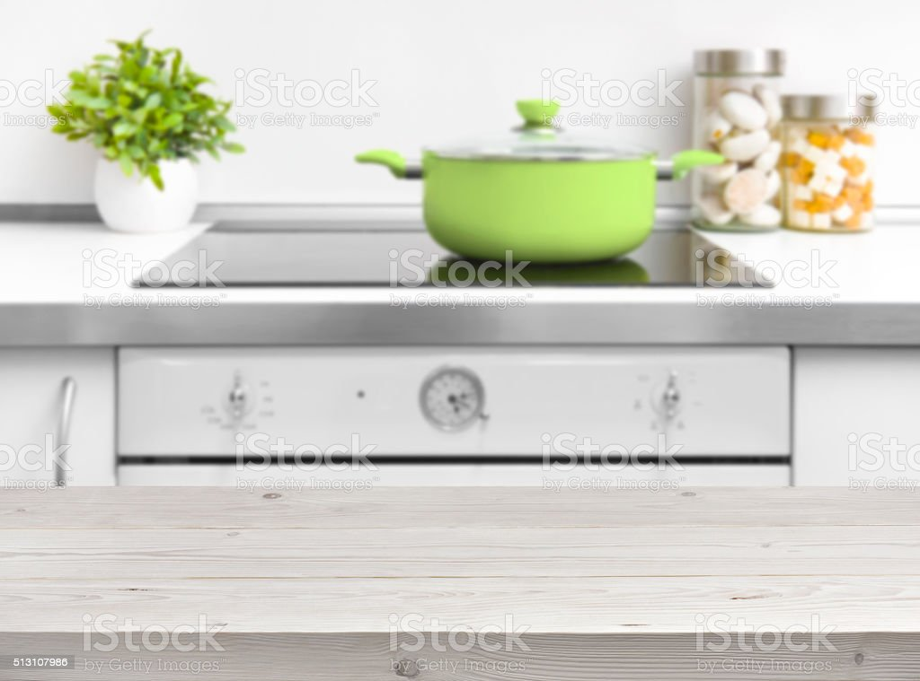 Wooden planks table top over kitchen bench and oven background stock photo