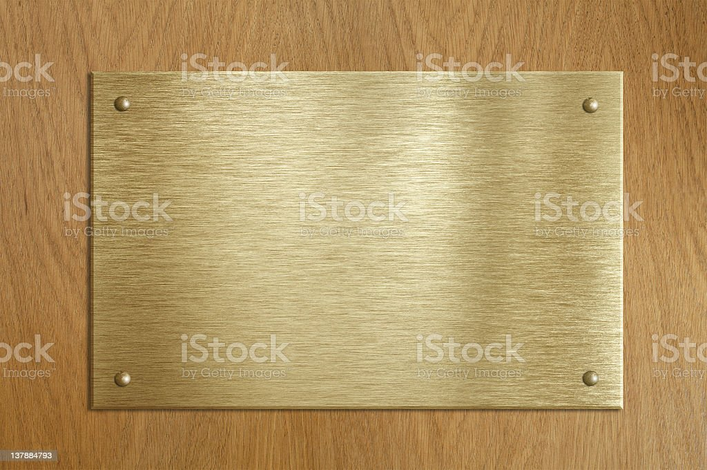 Wooden plaque with gold or brass plate stock photo
