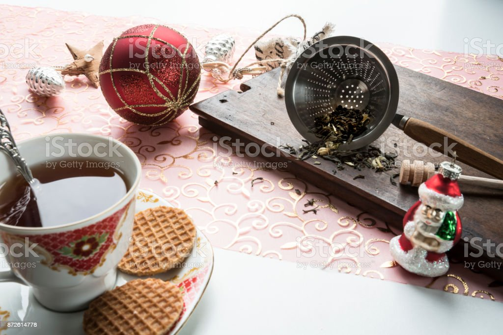 wooden plate with tea leaves in strainer, cup of tea, silver pine cones, Sante class, Christmas ball and Dutch stroopwafels 2 stock photo