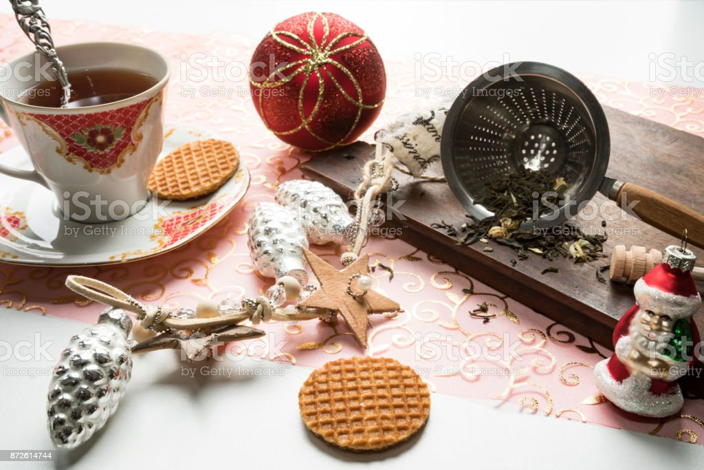 wooden plate with tea leaves in strainer, cup of tea, silver pineapple, Sante class, Christmas ball and Dutch stroopwafels 3 stock photo