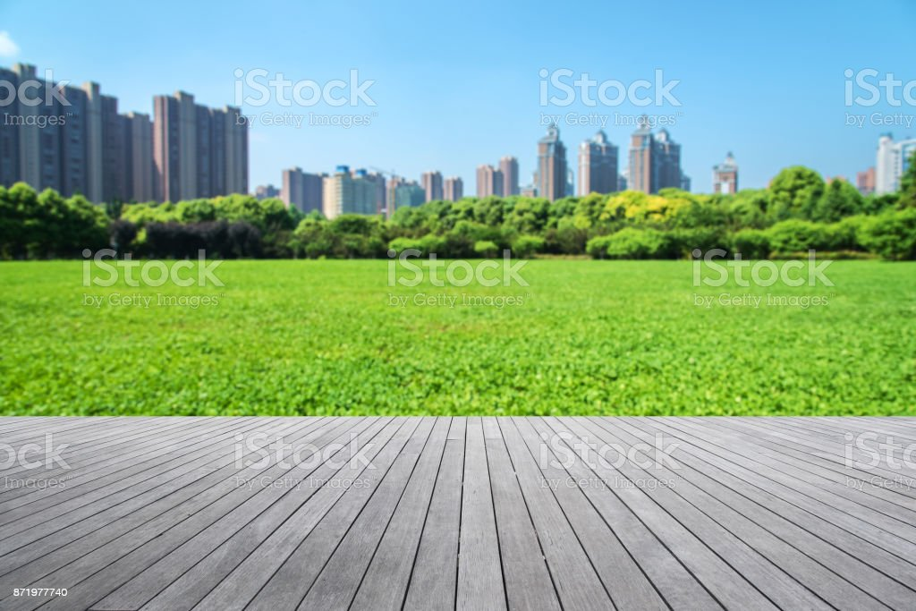Wooden platform and modern city central park abstract background stock photo