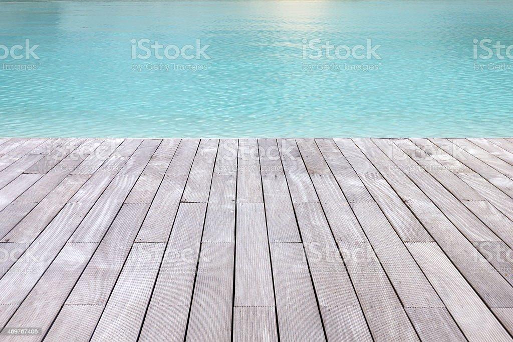 Wooden platform beside blue water. stock photo
