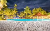 Wooden platform beside tropical swimming pool at night