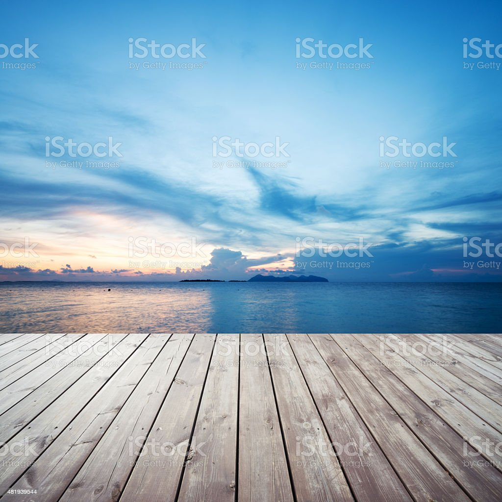 Wooden platform on beach with seascape and cloudy sky stock photo