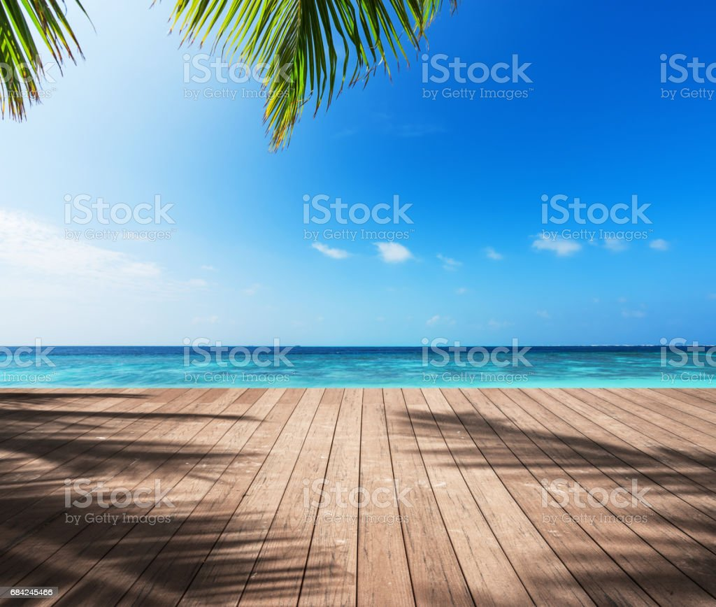 Wooden platform under palm trees beside tropical sea royalty-free stock photo