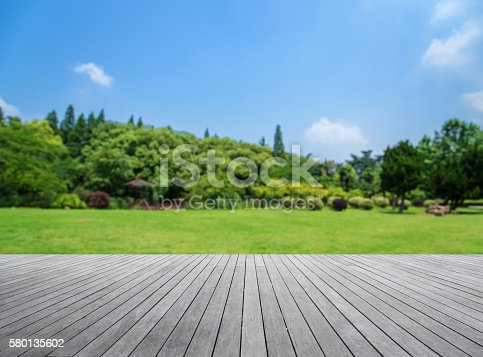 Wooden platform with green field defocused abstract background