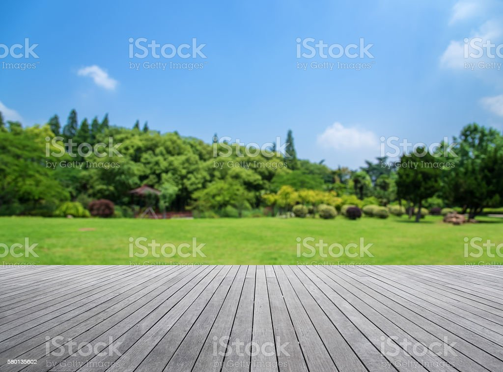Wooden platform with green field defocused abstract background stock photo