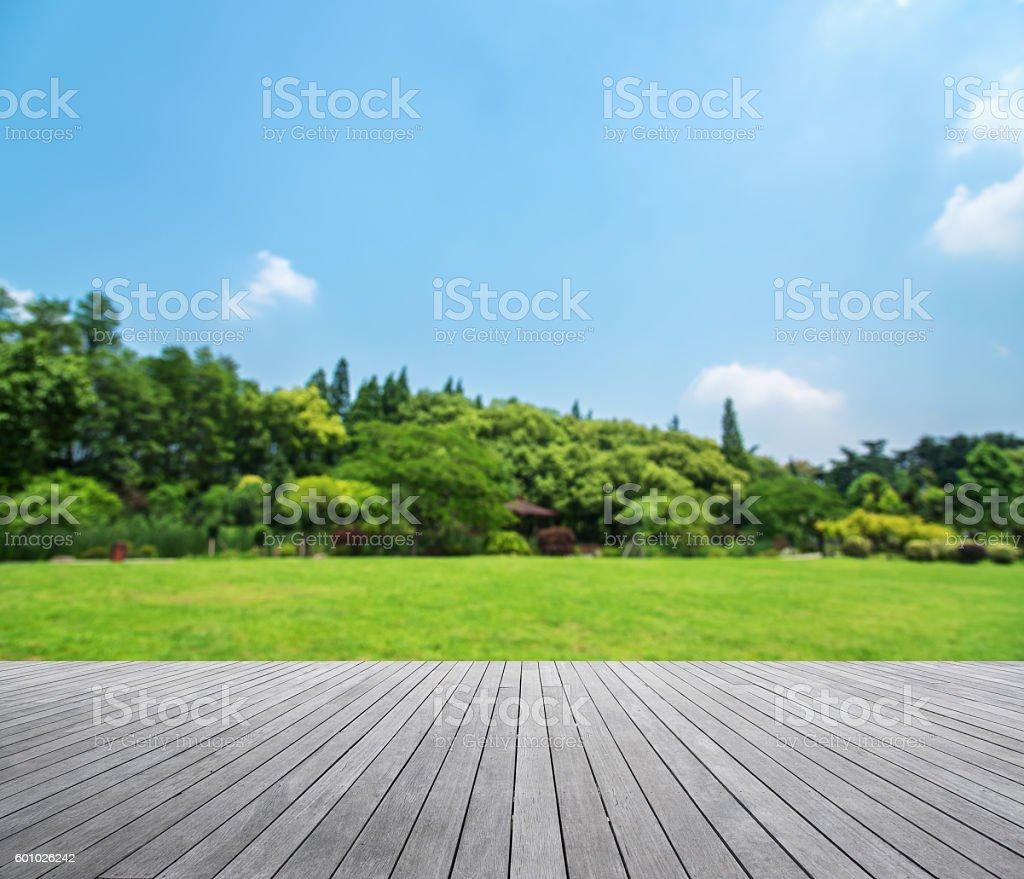 Wooden platform with green field defocused abstract background - foto de acervo