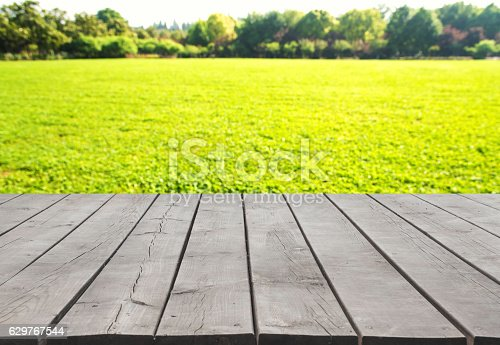 601026242istockphoto Wooden platform with green field defocused abstract background 629767544