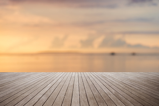 Wooden platform with sunset over the sea background