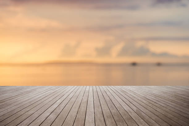 wooden platform with sunset over the sea background - pier stock photos and pictures