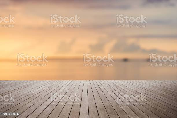 Photo of Wooden platform with sunset over the sea background