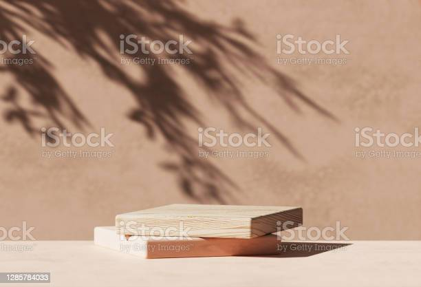 Photo of 3D  wooden podium display with leaf shadow. Copy space beige background. Cosmetics or beauty product promotion mockup.  Natural stone step pedestal. Trendy minimalist banner, 3D render illustration.