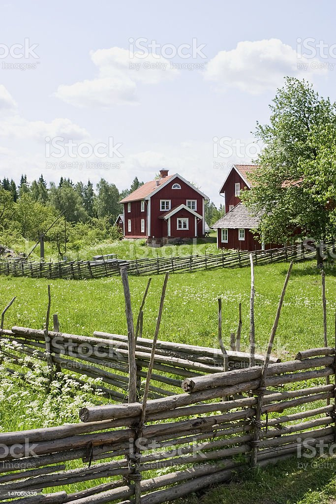 Wooden pole fence surrounding red barn and farmhouse royalty-free stock photo