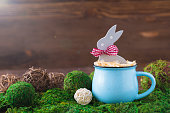 Wooden polka dot grey rabbit in a blue cup on the grass background, Easter postcard concept, toned