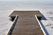 Wooden Pontoon Along A Frozen Lake With A Blue Sky