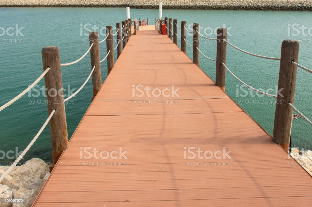 wooden port with rope on water stock photo
