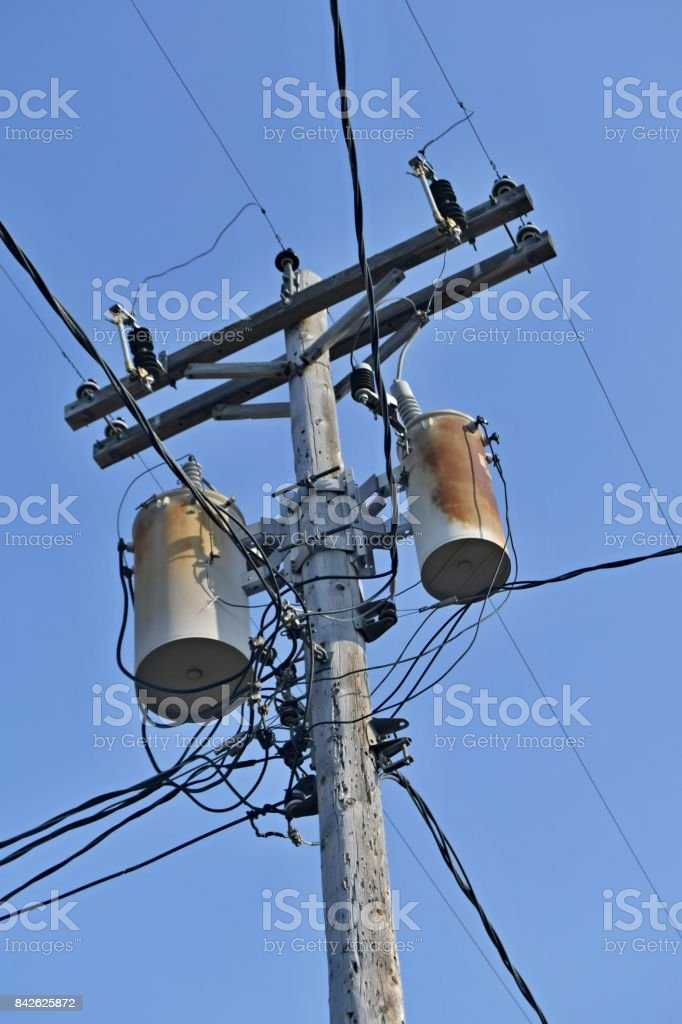 Wooden power utility pole with transformers and cables. stock photo
