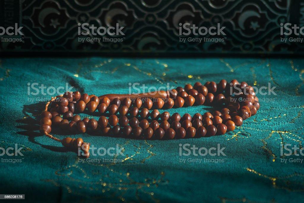 Wooden prayer beads under sunlight on a green velvet background stock photo