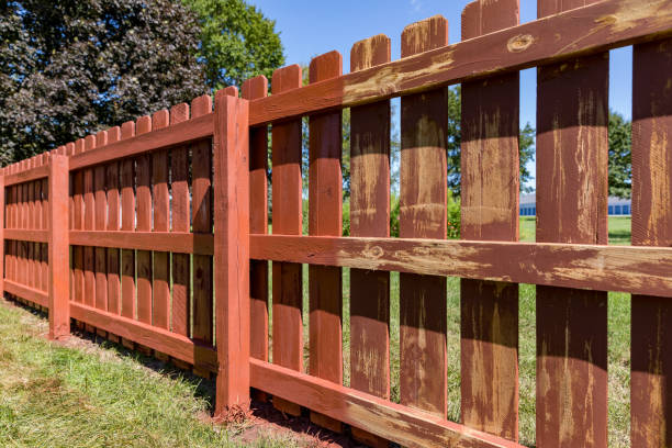 Wooden privacy fence in backyard with pickets being painted red stock photo