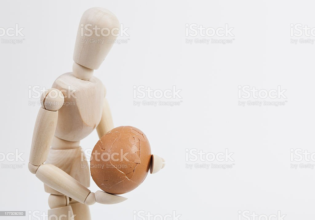 Wooden Puppet with a broken egg stock photo