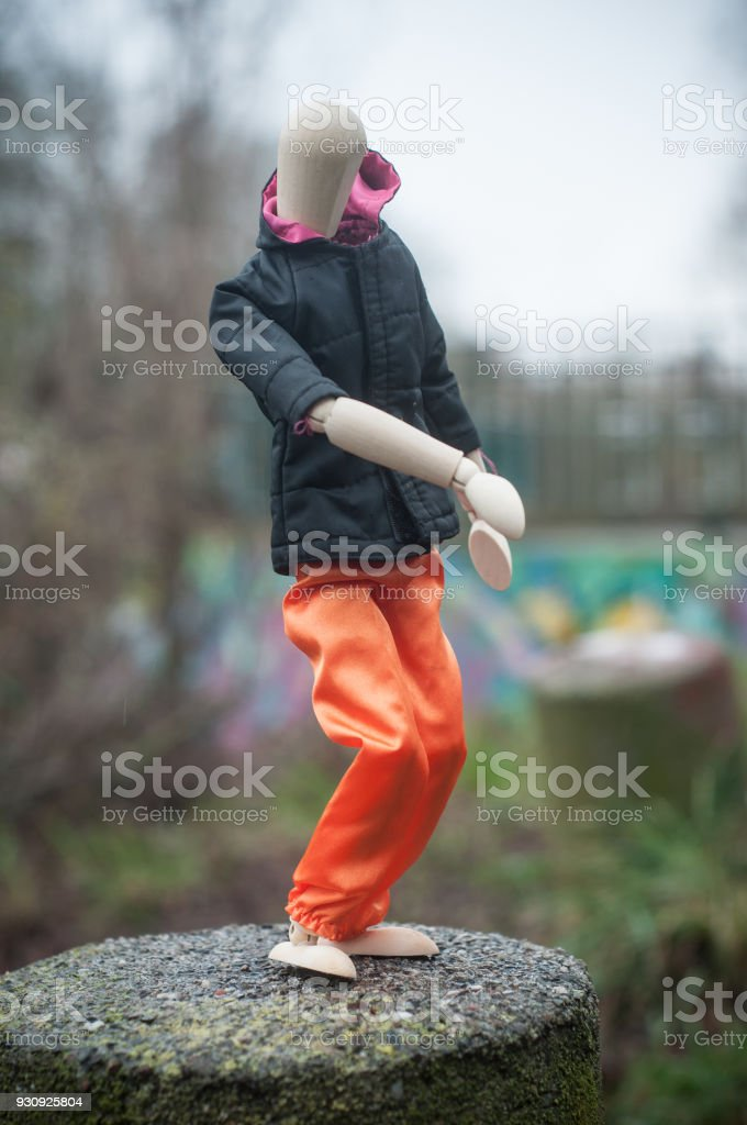 wooden puppet with street clothes in outdoor on graffti wal background - concept break dancing stock photo