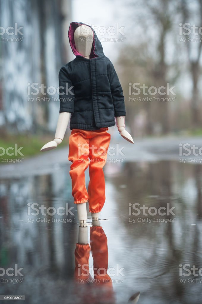 wooden puppet with street wear in a puddle in outdoor - concept break dancing stock photo