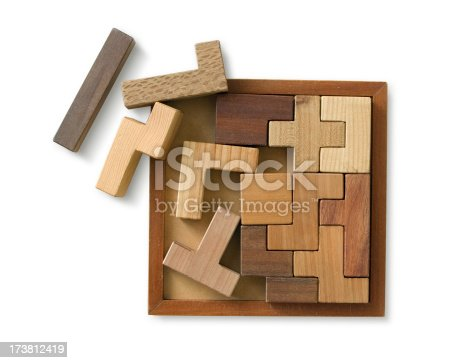 A wooden puzzle toy, isolated on white with a clipping path. Some of the pieces are out of the main puzzle. Taken from above.