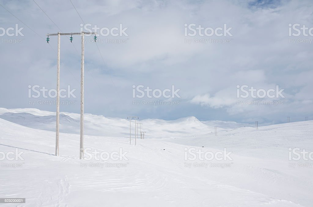 Wooden pylons and high voltage cables in winter mountains stock photo