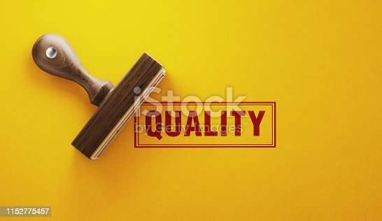 Wooden quality stamp on yellow background. Horizontal composition with copy space.