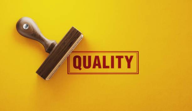 wooden quality stamp on yellow  background - kontrola jakości zdjęcia i obrazy z banku zdjęć