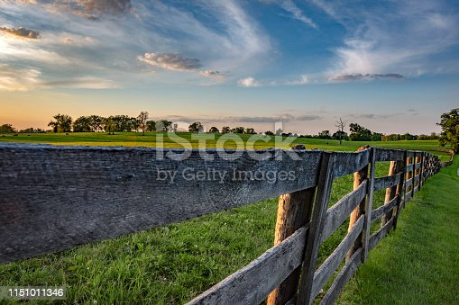 Weathered wooden rail fence seen at vanishing perspective in a lush bluegrass horse pasture lit by golden hour setting sun.