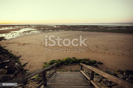 1088451256 istock photo Wooden railing that leads to the beach of Sanlucar de Barrameda 963868942