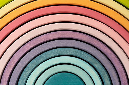 Colorful, arched building blocks. Pastel colored wooden rainbow stacker toy.