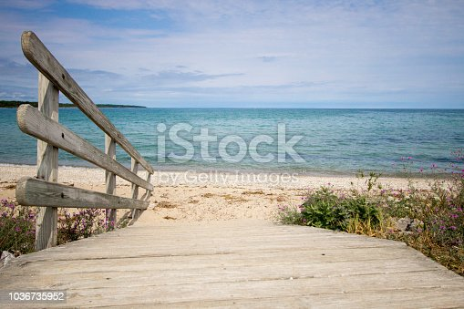 Wooden ramp to the blue waters of Lake Huron at the horizon. Color image in horizontal orientation with diminishing perspective.