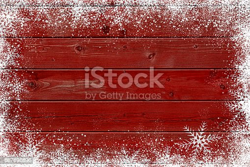 White snowflakes on red wood planks backdrop, with copy space available for text. Digital processing.