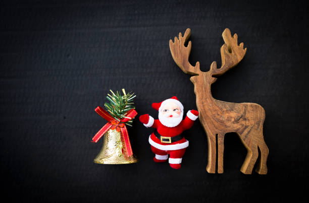 wooden reindeer with santa claus and golden bell on black background stock photo - Reindeer With Santa