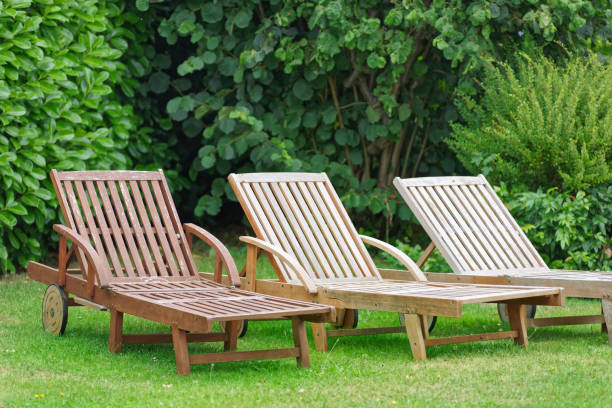 wooden relax loungers on a green lawn stock photo