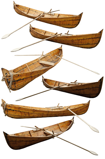 Wooden replica of a viking boat. Reconstruction of historic ships and boats. Wooden ship isolated on a white background. Medieval fishing boat with oars in different angles.