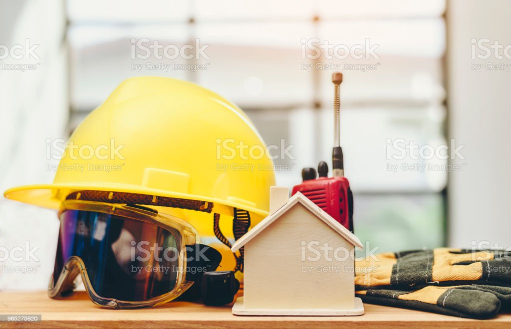 Wooden replicas, yellow helmets and accessories are placed on wooden floors.Standard and safe construction concept. zbiór zdjęć royalty-free