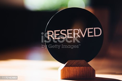Wooden reserved sign in restaurant on table. Table set. Capital letters. Reservation seat in cafeteria. Booking badge. Reserved logo. Toned image and blurred background.